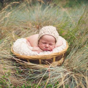 A sleeping baby in a knit hat nestled in a basket on top of a blanket in a grassy field.