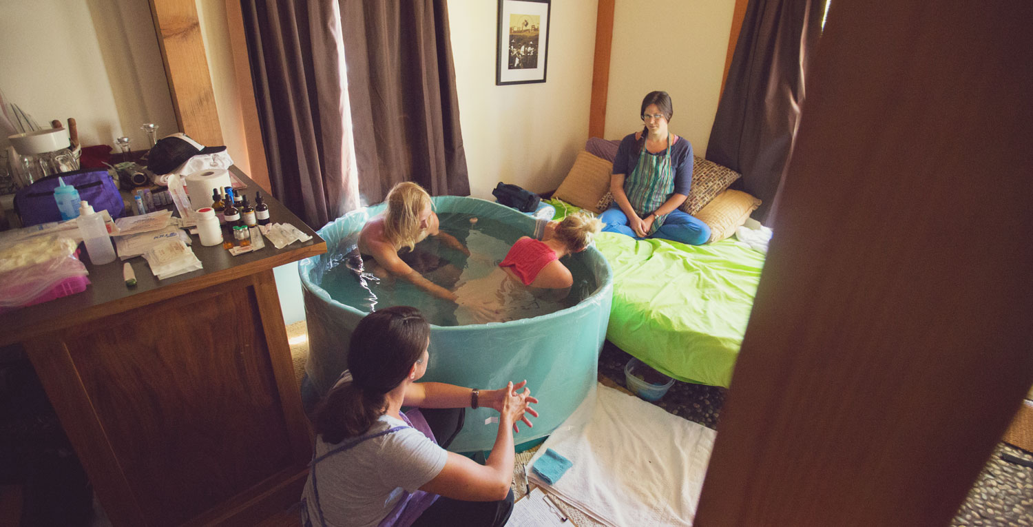 Photo of a woman giving labor in a birthing tub with her partner, surrounded by midwives.