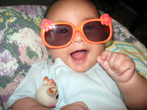 Photo of a happy baby wearing big orange sunglasses and hugging Sophie the Giraffe.