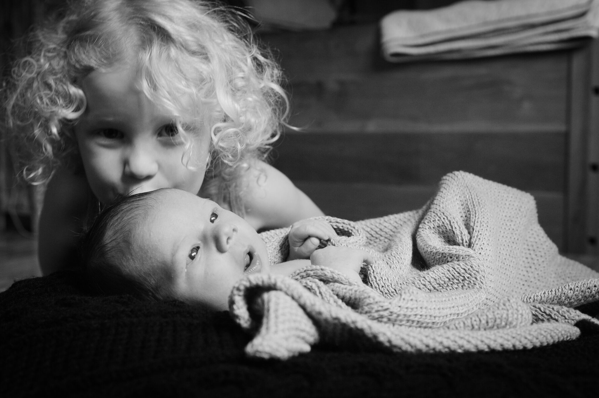 Black and white photo of a newborn baby wrapped in a blanket being kissed by a curly haired sibling.