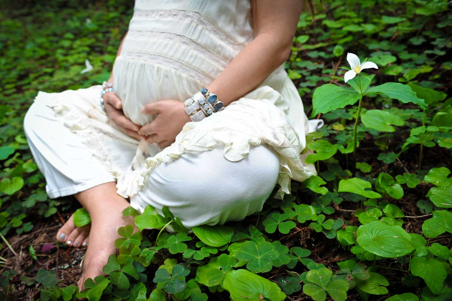 Photo of a pregnant woman in a white dress sitting amongst clover and trillium.