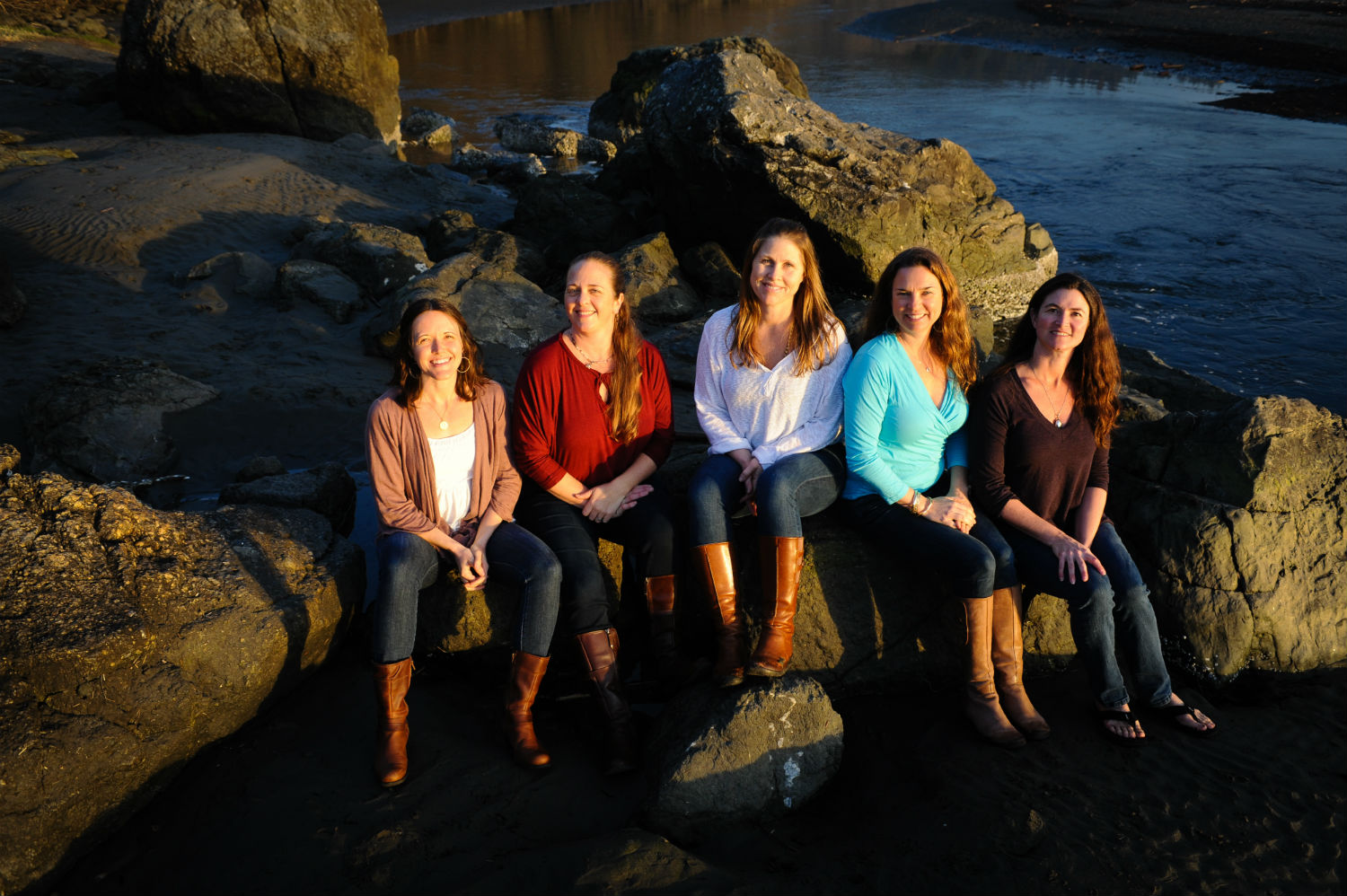 Moonstone Midwives team sitting on rocks above the ocean.